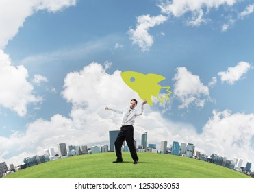 Confident and young businessman in suit starting launching a big rocket from his hand while standing on green meadow and with cloudy skyscape view on background.