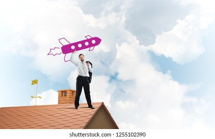 Confident and young businessman in suit starting launching a big rocket from his hand while standing on top of brick roof and with cloudy skyscape view on background.