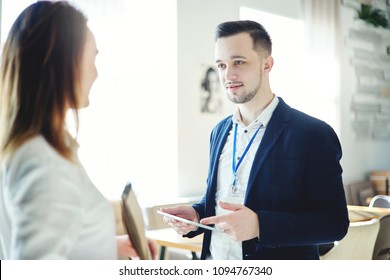 Confident young businessman with tablet computer in his hands and accreditation badge around his neck talking with unrecognizable female colleague at business event