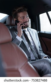 Confident young businessman talking on mobile phone and looking away while sitting on the back seat of a car