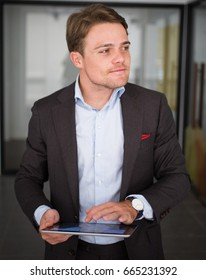 Confident young businessman using digital tablet