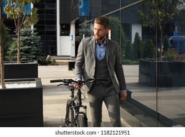 Confident young businessman walking with bicycle on the street in town