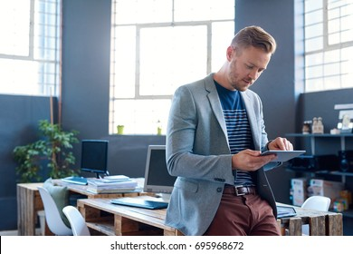 Confident young businessman wearing a blazer leaning against his desk in a large modern office working online with a digital tablet