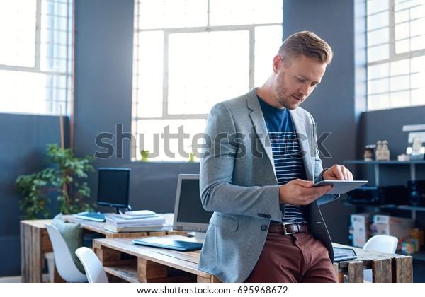 Уверенный молодой бизнесмен носит пиджак, прислоняясь к своему столу в большом современном офисе, работающего в Интернете с цифровым планшетом