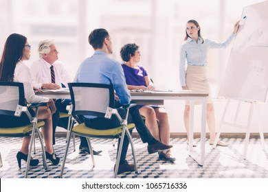 Confident young businesswoman or coach standing at flipchart at meeting and showing diagram to young and senior business people. Team listening attentively