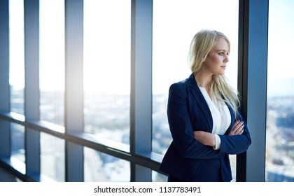 Confident young businesswoman deep in thought while standing with her arms crossed looking at the city skyline through office windows