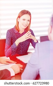 Confident young businesswoman discussing with male colleagues in board room