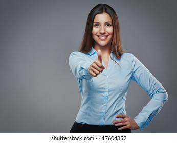 Confident young businesswoman giving the thumbs up against a gray background