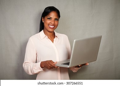 Confident young businesswoman holding a laptop while standing against grey texture background