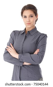 Confident young businesswoman standing arms crossed in grey blouse, smiling.?