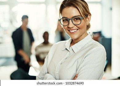 Confident young businesswoman standing in a modern office with her arms crossed with colleagues working at a table behind her