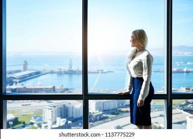 Confident young businesswoman staring thoughtfully through the windows of a modern office building overlooking the city skyline