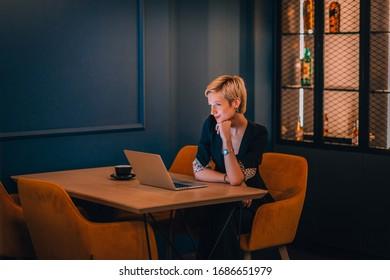 暗い青い壁を持つカフェの隅に座りながら、ノートパソコンで作業する自信のある若いビジネスマン
