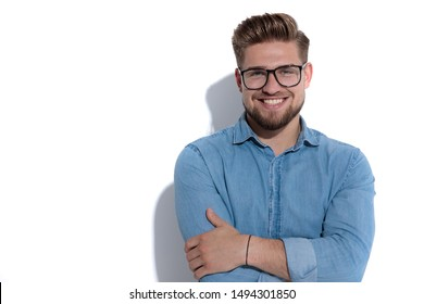 confident young casual man standing with hands crossed against white wall
