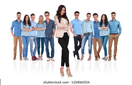 confident young casual team with businesswoman leader standing in front with crossed hands and legs, smiling on white background