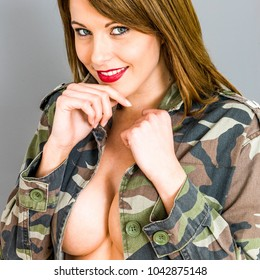Confident Young Caucasian Woman, With Brunette Hair, Posing Implied Topless In An Open Army Or Military Camouflage Jacket, Isolated On Grey, Large Natural Breasts And Cleavage