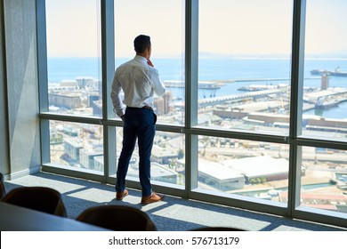 Confident young executive deep in thought while looking through the windows of a boardroom at the city from high up in a modern office
