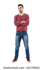 Confident young fashion male model with folded hands looking at camera.  Full body length portrait isolated over white background.