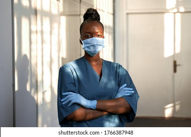 Confident young female african scrub nurse wear blue uniform, face mask, gloves standing arms crossed in hospital hallway. Black millennial woman doctor, surgeon, medic staff professional portrait.
