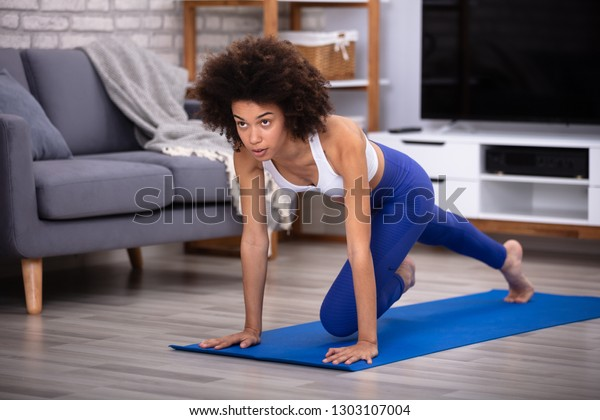 Confident Young Female Athlete In Sportswear Exercising On Fitness Mat At Home