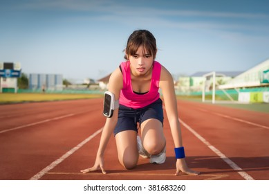 Confident young female athlete in starting position ready to start a sprint.