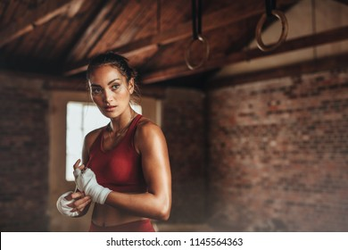 Confident young female boxer wearing strap on wrist. Boxing practice at gym. Woman in sports clothing preparing for boxing fight or workout.
