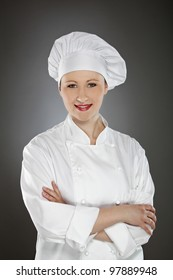 Confident young female chef with arms crossed