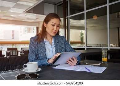 Confident young female financier with touch pad in hand is reading financial news in network ,while is sitting near  office window