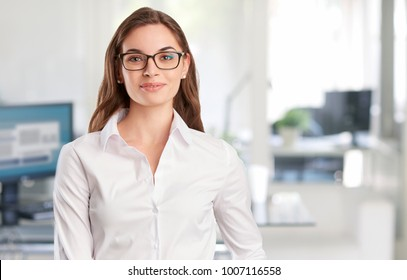 A confident young financial businesswoman standing at the office and looking at camera.