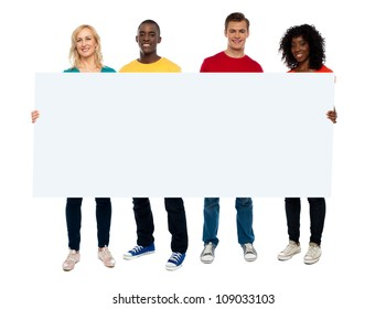 Confident young group showing blank poster, full length portrait