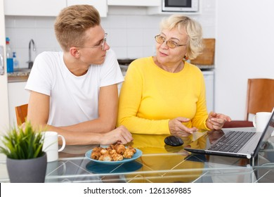 Confident young guy helping his mother with laptop at kitchen