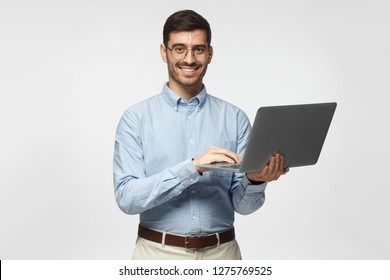 Confident young handsome business man in blue shirt holding laptop and smiling at camera, isolated on gray background