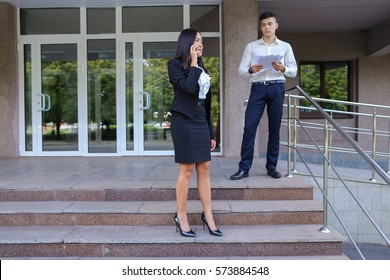 Confident young handsome male man holds documents, decides work issues, make appointment and  stands near  female, asian business woman talks on modile phone and negotiating with business partne