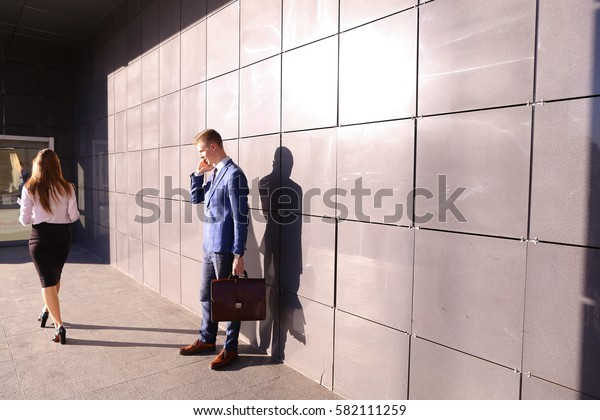 Confident young handsome male man holding smart phone and talking on it, decides work issues, make appointment, negotiating with business partners, passes by young modern girl and carries folder with