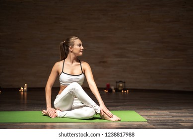 Confident young lady sitting on the yoga mat with candles on the background and smiling while twisting and doing asanas