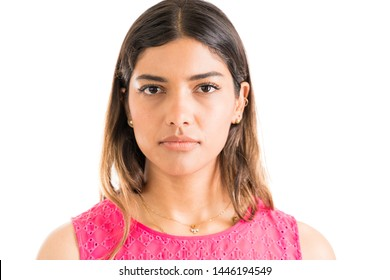 Confident young Latin woman with serious face making eye contact in studio