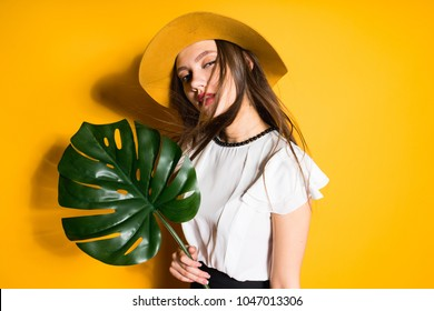 confident young long-haired girl model in a fashionable hat holds a green leaf and poses