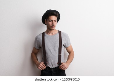 A confident young man with hat in a studio, holding suspenders.