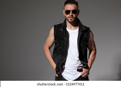 Confident young man holding both hands in his pockets while wearing sunglasses and a black jeans vest, standing on gray studio background
