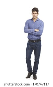 Confident young man in jeans and shirt standing arms crossed.