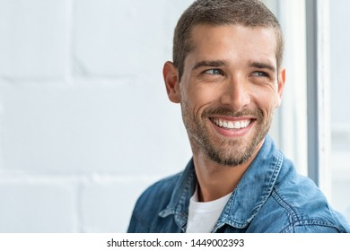 Confident young man looking away with big smile. Happy handsome guy looking through window thinking about the future. Closeup face of smiling casual man imagine with copy space.