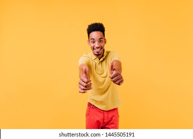 Confident young man looking right to camera and showing thumbs up. Indoor photo of enthusiastic stylish guy.