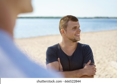 Confident young man on the beach watching with a smile