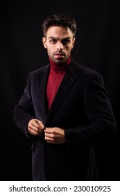 Confident young man on black background.