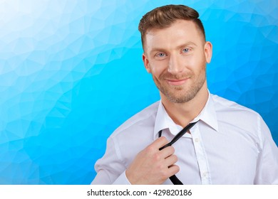 Confident young man in shirt and tie  adjusting his necktie