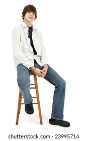 Confident young man sitting on a wooden stool