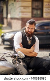 Confident young man  sitting on a motorbike with his arms crossed