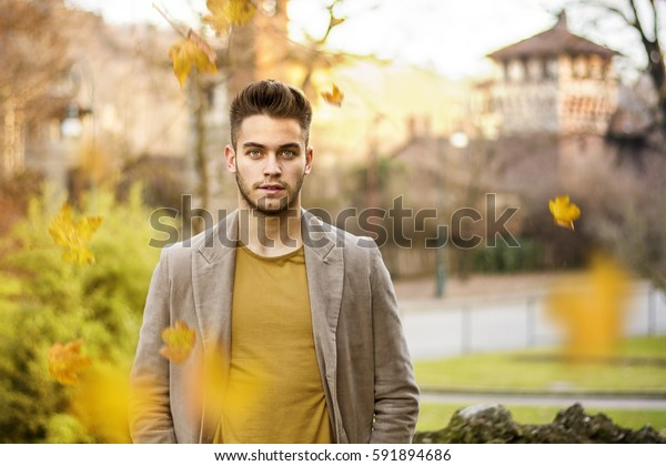 Confident young man standing in the autumn park with ancient castle in background and falling leaves in foreground. Horizontal outdoors shot.