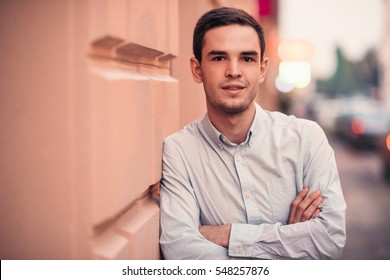 Confident young man standing on a city sidewalk