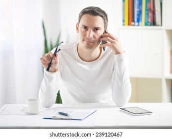 Confident young man talking on the phone while working at home